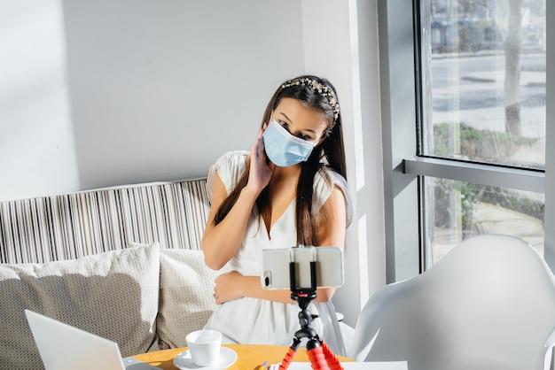 Uma jovem está sentada em um café com uma máscara e conduz um videoblog.