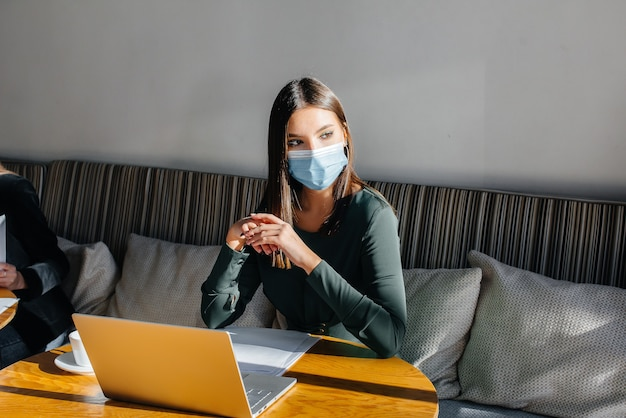 Uma jovem está sentada em um café usando uma máscara e trabalhando em um computador