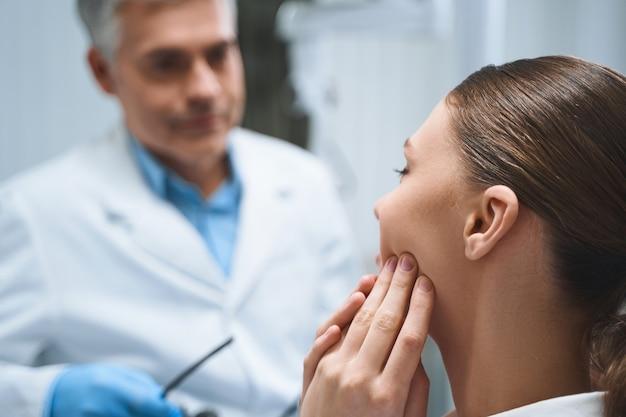 Uma jovem está sentada em uma clínica dentária reclamando de problemas na boca para um médico experiente