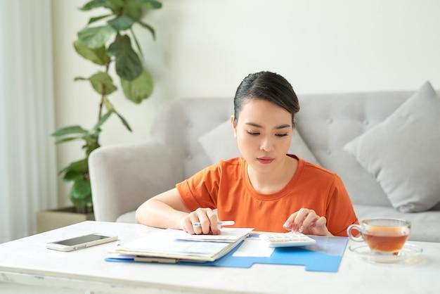 Uma jovem está sentada na sala de estar olhando seus recibos em casa