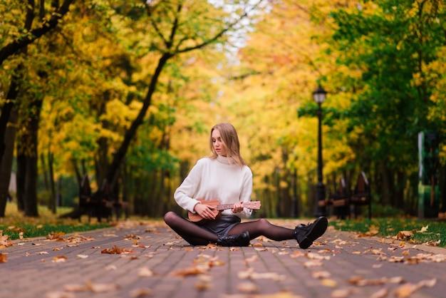 Uma jovem está sentada no banco do parque tocando cavaquinho e posando com o violão