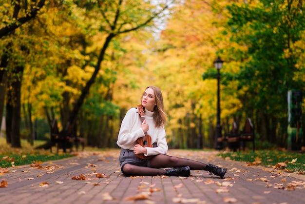 Uma jovem está sentada no banco do parque tocando cavaquinho