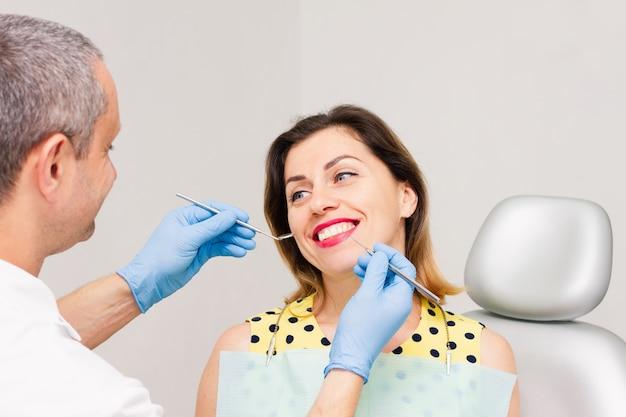 Uma jovem está sentada no consultório do dentista.