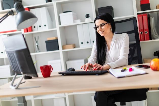 Uma jovem está sentado à mesa e digitar o texto no teclado.
