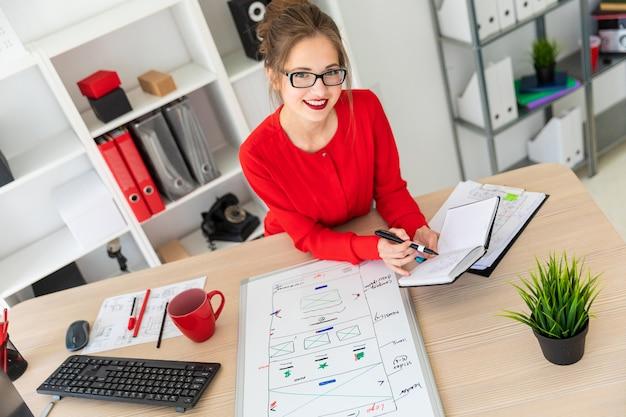 Uma jovem está sentado à mesa no escritório