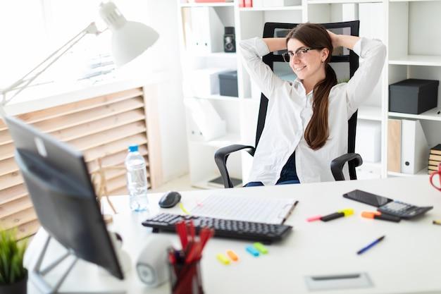 Uma jovem está sentado em uma mesa no escritório, colocando as mãos atrás da cabeça e olhando para o monitor.