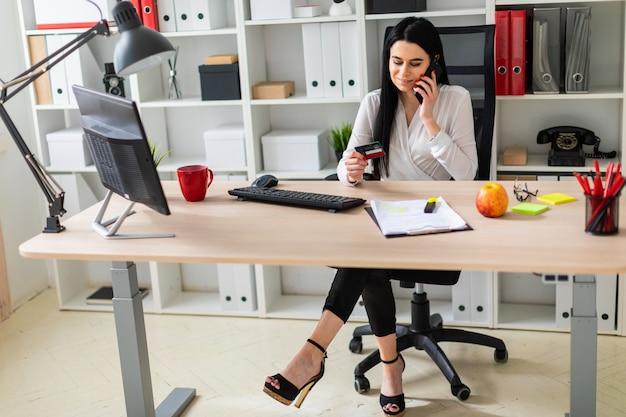 Uma jovem está sentado em uma mesa, segurando um cartão de banco na mão e falando ao telefone.