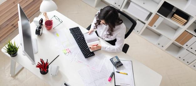 Uma jovem está sentado na mesa do computador no escritório, segurando uma caneta na mão e olhando para o bloco de notas.