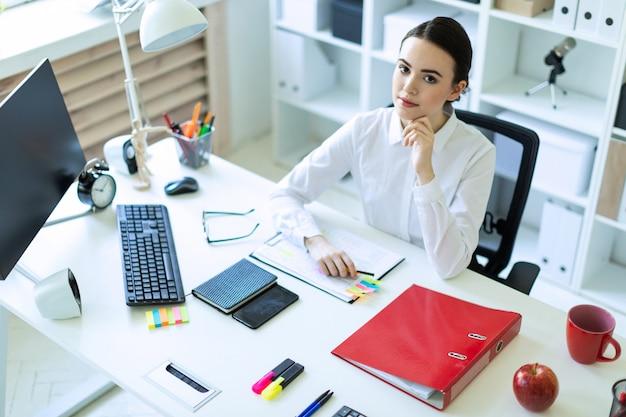 Uma jovem está sentado na mesa do computador no escritório.