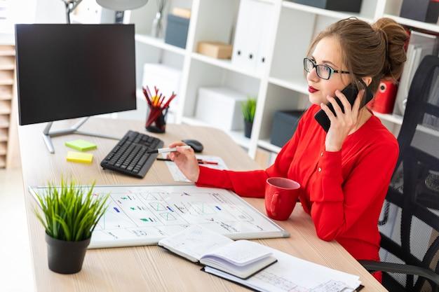 Uma jovem está sentado na mesa do escritório, segurando um marcador na mão