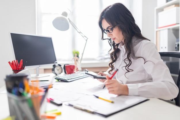 Uma jovem está sentado na mesa do escritório, trabalhando com uma calculadora e documentos.
