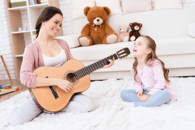 Uma jovem está tocando violão e uma garota está cantando.