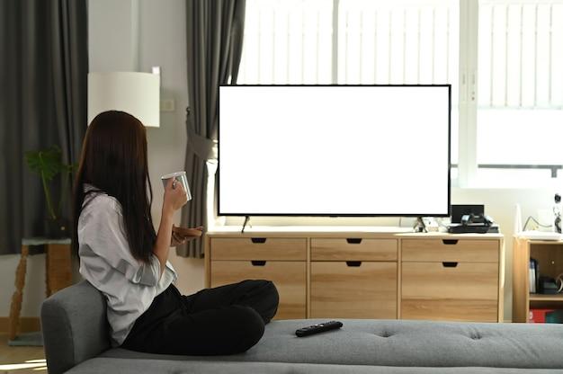 Uma jovem está tomando café e assistindo televisão no sofá em casa.