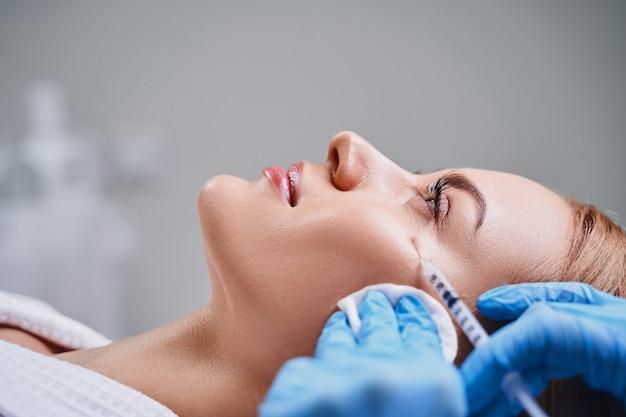 Uma jovem está visitando um cosmetologista e recebendo injeções de beleza para rejuvenescer o rosto e levantar a pele