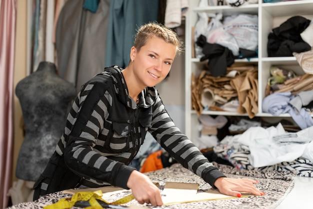 Uma jovem estilista de roupas. medidas por centímetro de linha de corte no tecido para confecção de roupas. confecção de roupas sob encomenda, conceito de designer de moda