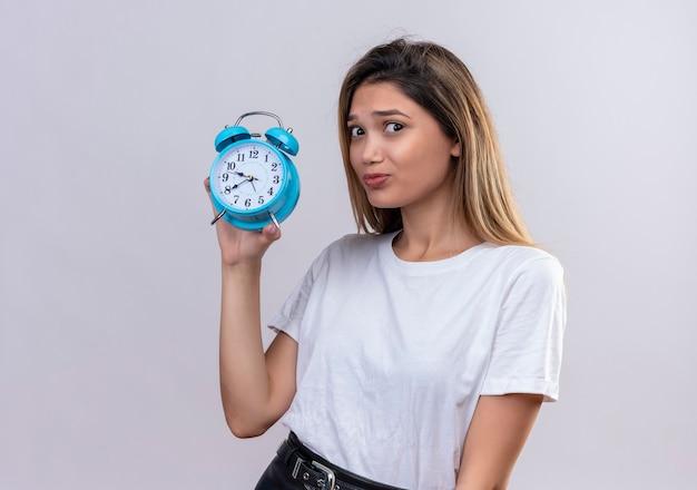 Uma jovem estressante em uma camiseta branca mostrando um despertador azul
