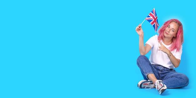 Uma jovem estudante aponta para a bandeira da grã-bretanha, incentivando-a a aprender inglês sobre fundo azul.