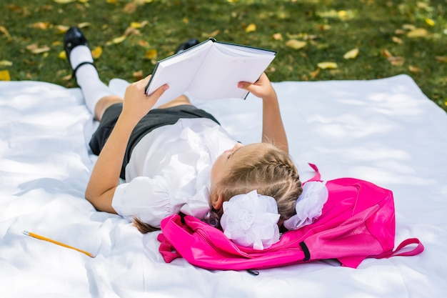 Uma jovem estudante faz a lição de casa enquanto está deitada em uma mochila em um parque ensolarado de outono. educação ao ar livre para crianças. de volta ao conceito de escola. copie o espaço