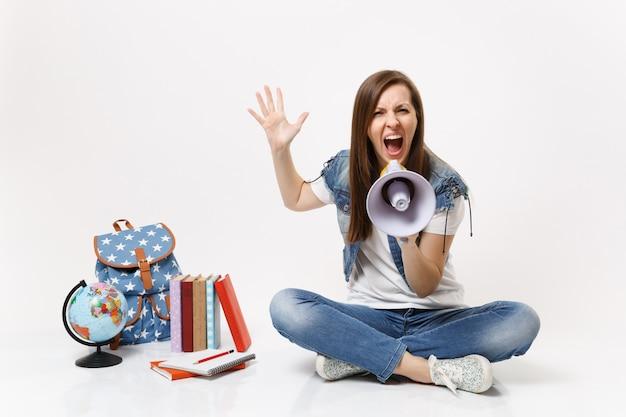 Uma jovem estudante irritada com raiva grita segurando um megafone, espalhando a mão, sentada perto do globo, mochila, livros escolares isolados