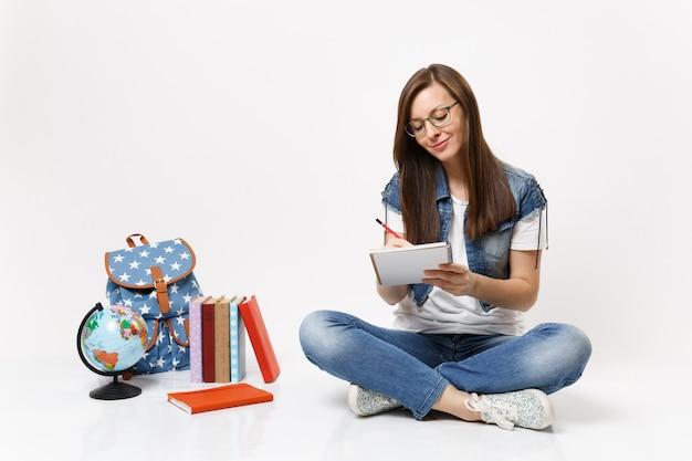 Uma jovem estudante muito sorridente de óculos escrevendo notas no caderno, sentada perto do globo, mochila, livros escolares isolados