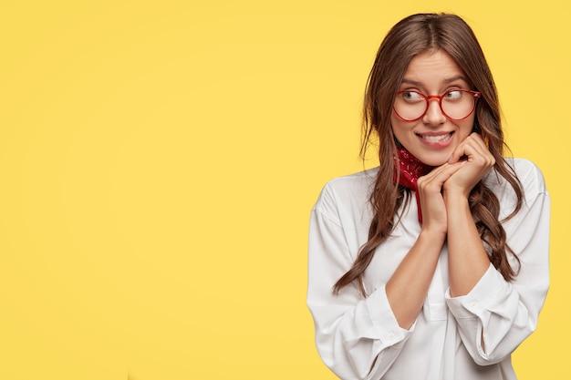 Uma jovem europeia bonita e sonhadora mantém as mãos embaixo do queixo, olhando de lado com uma expressão misteriosa