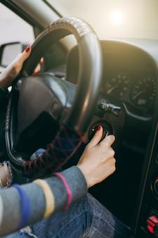 Uma jovem europeia com pele limpa e saudável colocou as mãos com manicure vermelha nas unhas no volante do carro e na chave de ignição. viajar e dirigir o conceito.