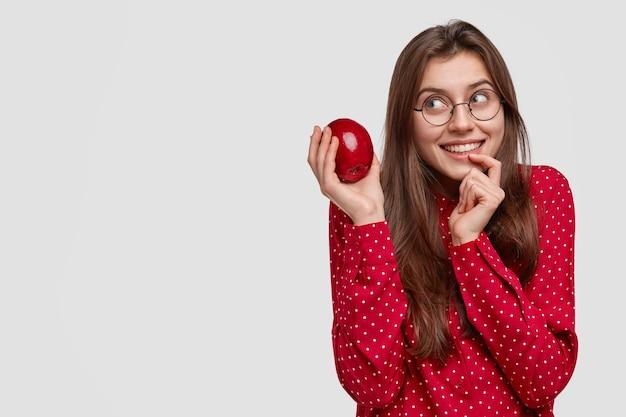 Uma jovem europeia sonhadora mantém o dedo perto dos lábios, segura uma deliciosa maçã fresca, pensa em cozinhar uma torta