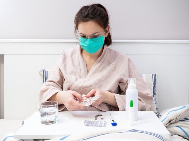 Uma jovem européia tem um coronavírus e está sendo tratada em um hospital. uma mulher com uma máscara médica toma pílula