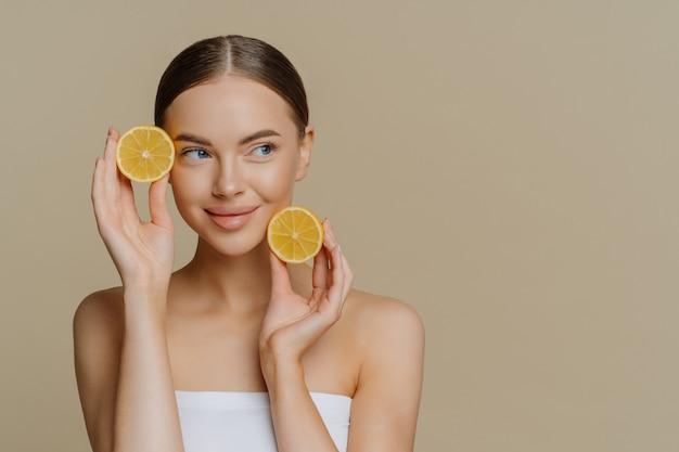Uma jovem europeia usa frutas caseiras como máscara facial segurando rodelas de limão