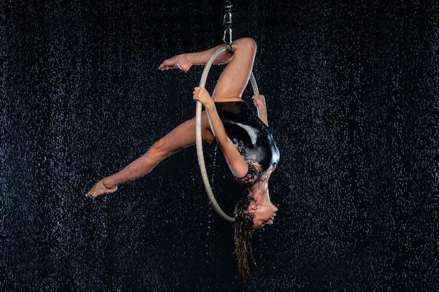 Uma jovem executa os elementos acrobáticos no anel aéreo. apresentações de tiro do aqua studio em um fundo preto.