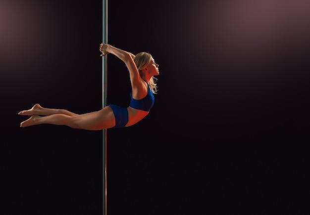Uma jovem executa um elemento em um poste fazendo uma curva no estúdio de dança, em um quarto escuro e isolado.