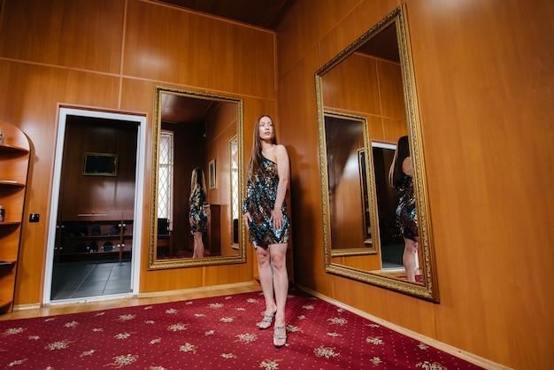 Uma jovem experimenta roupas novas no provador da loja. Foto Premium