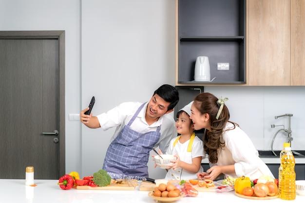 Uma jovem família asiática está preparando uma salada na cozinha e o pai tira uma foto de selfie ao telefone