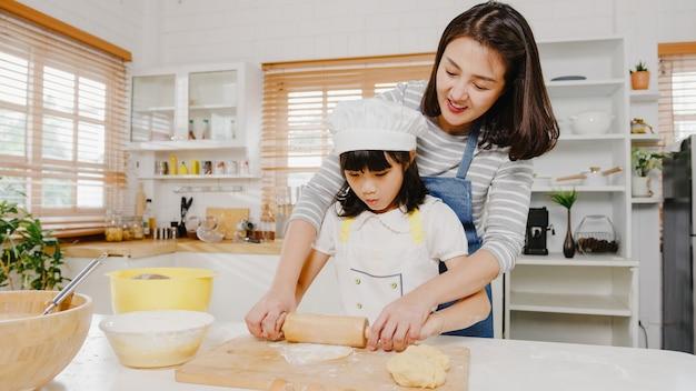 Uma jovem família asiática japonesa e feliz e sorridente com crianças em idade pré-escolar se divertem cozinhando bolos