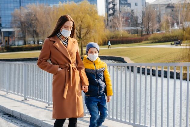 Uma jovem família caminha e respira ar fresco em um dia ensolarado durante uma quarentena e uma pandemia. máscaras no rosto das pessoas.
