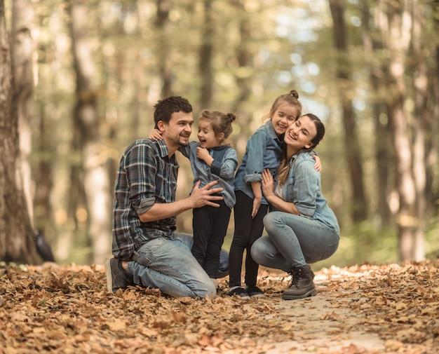 Uma jovem família caminha na floresta de outono com crianças.