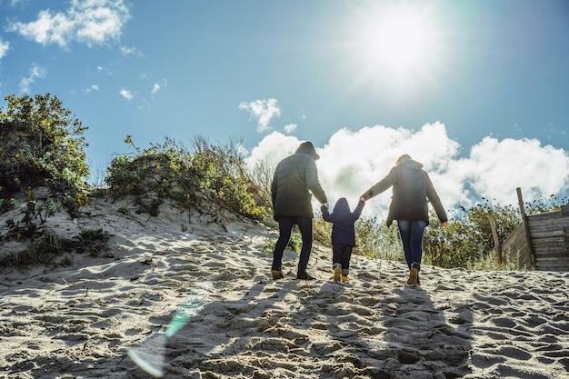 Uma jovem família com filhos passa o fim de semana nas margens do frio mar báltico