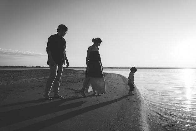Uma jovem família com um filho de 3 anos caminha pela praia selvagem à noite. foto em preto e branco