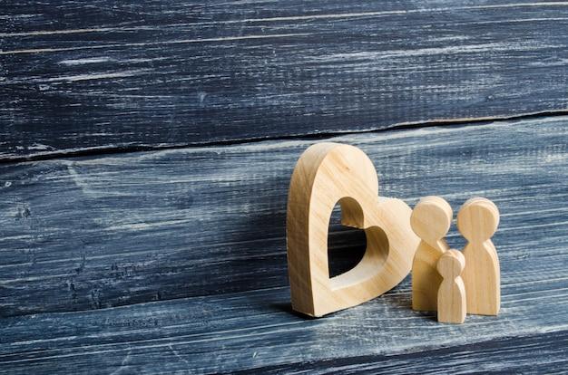 Uma jovem família com uma criança está de pé perto de um coração de madeira.