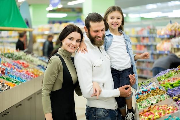 Uma jovem família com uma filha escolhe doces e chocolates em uma grande loja, supermercado.