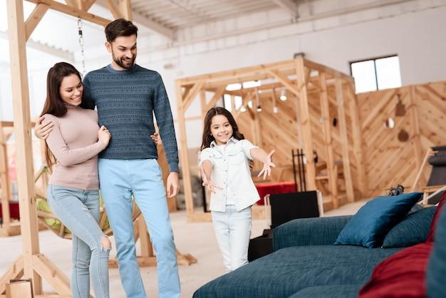 Uma jovem família com uma menina está escolhendo um novo sofá.