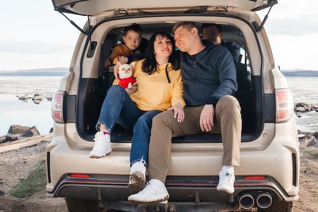 Uma jovem família está relaxando na margem do rio, sentado no porta-malas de um carro. pais jovens com dois filhos e um cachorro chihuahua. recreação e turismo.