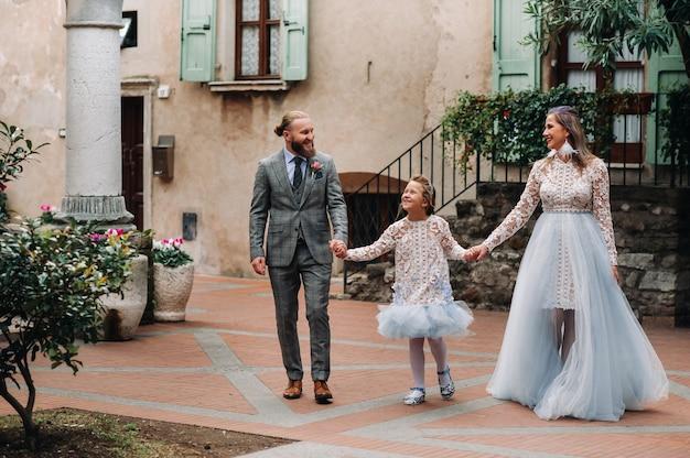 Uma jovem família feliz caminha pela cidade velha de sirmione, na itália. família elegante na itália em uma caminhada
