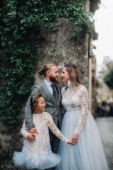 Uma jovem família feliz caminha pela cidade velha de sirmione, na itália. família elegante na itália em uma caminhada.