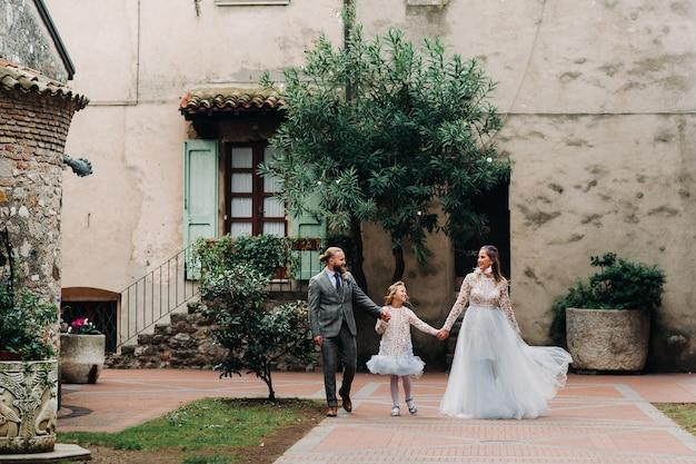 Uma jovem família feliz caminha pela cidade velha de sirmione, na itália