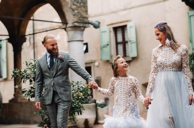 Uma jovem família feliz caminha pela cidade velha de sirmione, na itália.