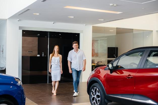 Uma jovem família feliz escolhe e compra um carro novo em uma concessionária