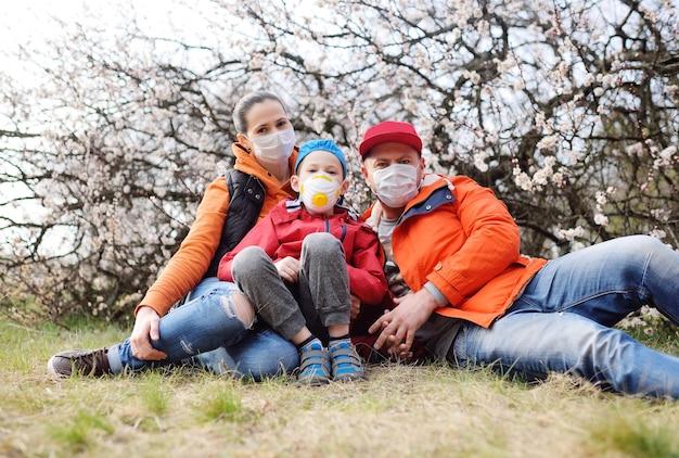 Uma jovem família-mãe, pai e filho com máscaras médicas e respiradores no contexto de flores de damasco na primavera durante a pandemia de coronavírus covid-19