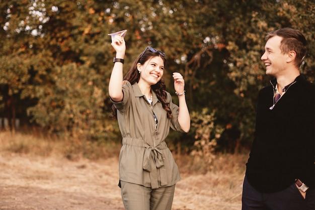 Uma jovem família se divertindo ao ar livre, jogando avião de papel, sentindo-se feliz, sorrindo e rindo