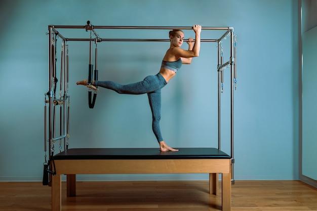 Uma jovem faz exercícios de pilates com um reformador de cama